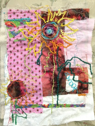 Collaged fabrics with sunflower drawing embroidered on top.